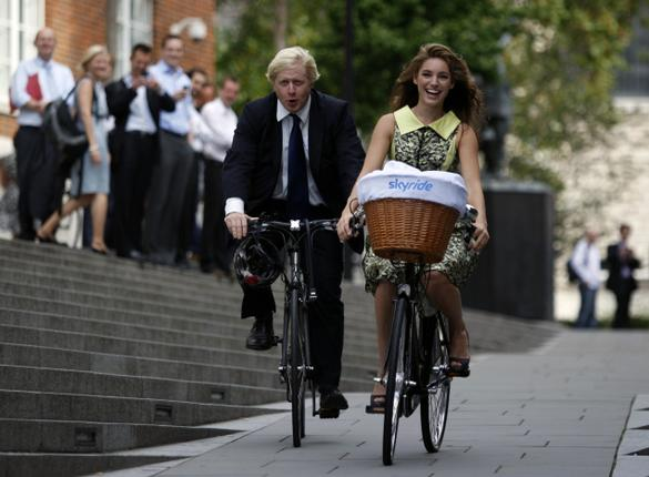 London Mayor Boris Johnson and model Kelly Brook cycle as they pose for the photographers for the launch of Skyride, a free cycling event, in central London