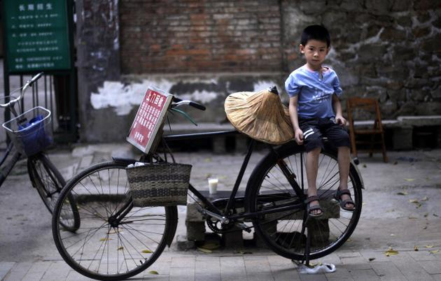 Bike sharing programme, Chinese kid sitting on bicycle